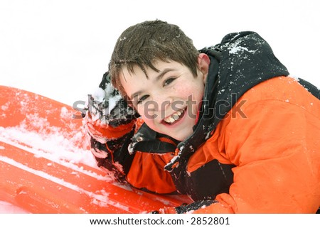 A Boy Smiling Laying on his Sled