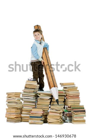 A boy standing on a pile of books and holding a huge pencil. Education. Isolated over white.