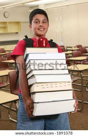 A boy student carrying a large stack of books in the classroom