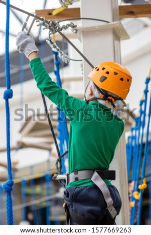 a boy takes a risk by taking a dangerous route in a rope  Park