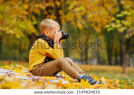 a boy takes pictures, a child with a camera in the fall