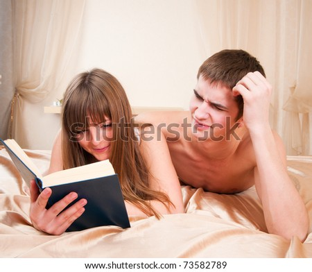 A boy trying to get some attention from his girlfriend, who's busy reading a book.