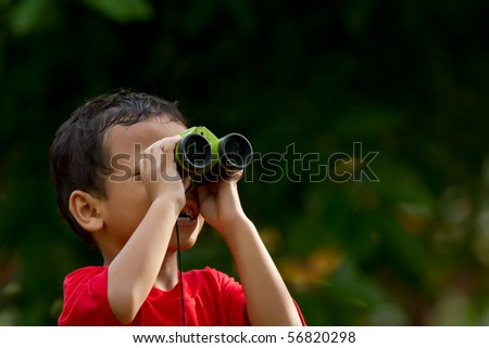 A boy uses binocular to view long distance subject
