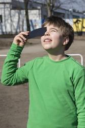 A boy watching a solar eclipse through a dark glass. Poland.