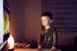 A boy watching cartoons on television. The boy is standing in a closed room in front of the TV and leaning on a table staring at a cartoon. Occupation before bed, cartoon for good night
