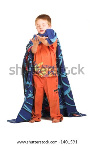 A boy wearing a blanket as a cape, holding out his hand.  Eyes closed.