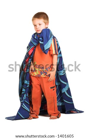 A boy wearing a blanket as a cape, looking sad.