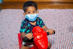 A boy wearing a surgical protective face mask and playing with a toy horse at home during coronavirus pandemic.