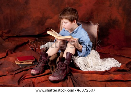 a boy wearing old shoes is sitting in a case and reading a book