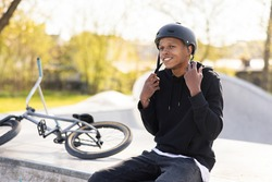 A boy who has fallen off bike, a bmx, and is sitting on a concrete ramp, gets ready to ride back on the track with friends, puts helmet on his head and fastens it under neck