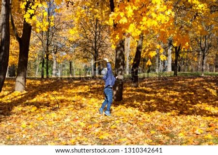A boy who sticks at the foliage of trees in the autumn season, self-indulgence