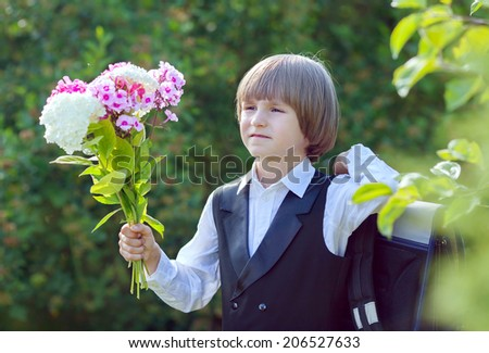a boy with a bouquet goes to school on the first of September