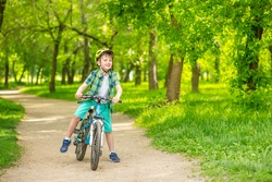 A boy with a green bicycle helmet on his head rides his bicycle in the summer park. Summer rest