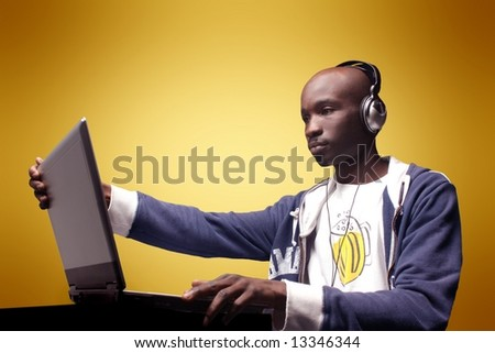 a boy with a laptop and ear-phones