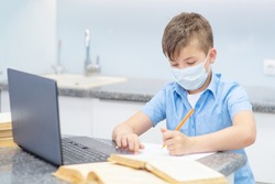 A boy with a medical mask on his face at home in the kitchen is engaged in education using a laptop. The boy writes a task in a notebook. Education during quarantine concept