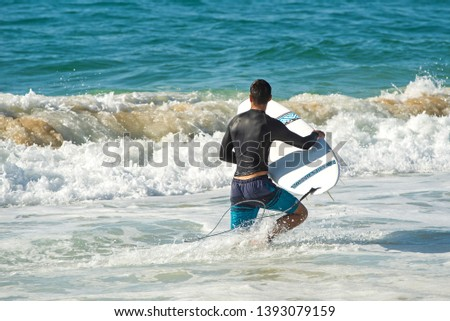 A boy with a wetsuit is entering in the ocean with its surfboard and is about to start a surf session #1393079159
