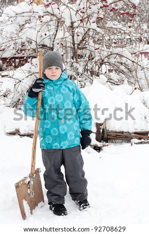 A boy with a wooden shovel for snow removal