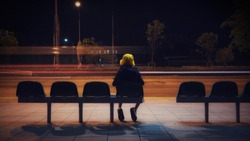 A boy with a yellow hat sitting at the bus stop alone at night. Background has a blurred motion of passing by car lights.