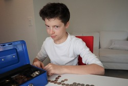 A boy with light skin and brown hair secretly counting out his allowance money. A blue lock box is on the table. He is wearing a white shirt.