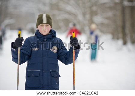 a boy with skiis in the park