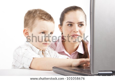 A boy with young woman are working with the laptop. The boy uses of computer. He is learning, maybe plays on game. She's watching what he does.