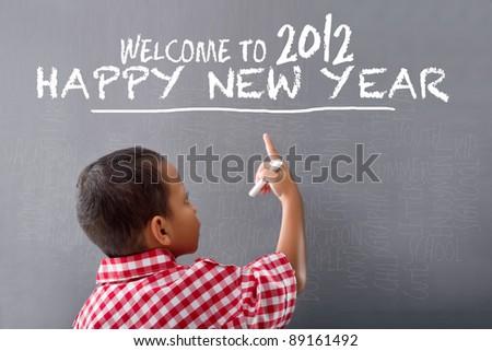 A boy writes happy new year 2012 on blackboard