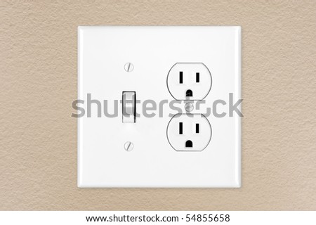 A brand new modern electrical toggle light switch and power outlet on a freshly painted wall.