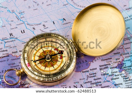 A brass compass laid on a map of Russia - stock photo