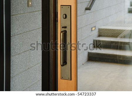 A brass door handle with turning lock knob and thumb latch. A small set of steps are reflected in the glass. Horizontal shot.