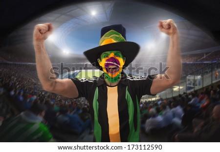A brazilian football fan celebrating a goal in a football stadium.