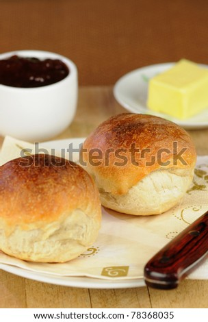 A bread roll cut in half in a layout with butter and strawberry jam.