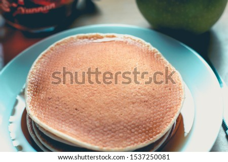 A breakast made of pancakes soaking in mapple syrup, a cup of tea and a granny smith apple. focus on the pancakes