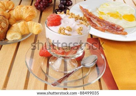 A breakfast feast with a yogurt parfait, bacon, eggs and croissants
