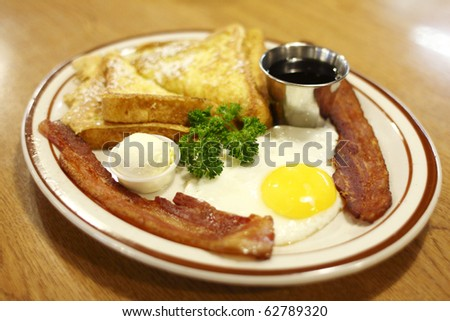 A breakfast of French toast, bacon, and an egg.