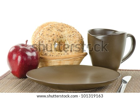 A breakfast place setting with bagels coffee and an apple.