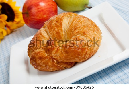 A breakfast plate including a croissant, plate, red and green apples,  and a sunflower on a blue gingham table cloth