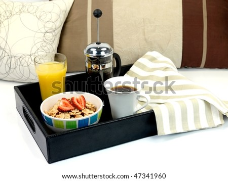 A breakfast tray with fresh coffee, cereal and orange juice
