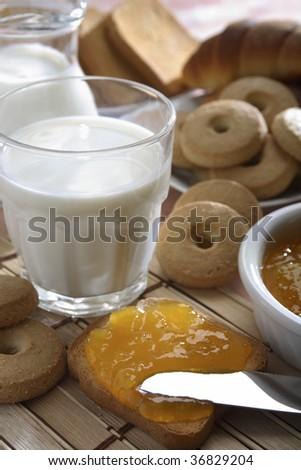 A breakfast with milk, bisquit, jam, bread