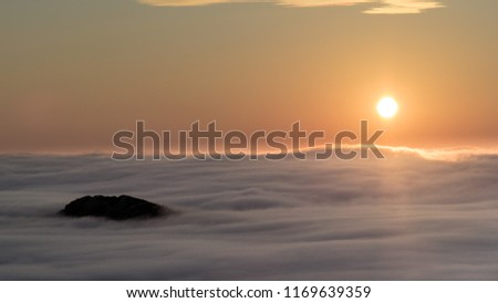 A breathtaking landscape in Taiwan. This was taken on top of a mountain. The clouds formation is vast and dramatic. The sun rises above the thick clouds. The image is calm, peaceful and magnificent. #1169639359