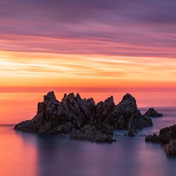 A breathtaking scenery of sea stacks during sunset under the colorful sky in Guernsey