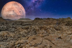 A breathtaking shot of an alien planet rocky surface on a starry sky and a big planet background- perfect for alien planet concept