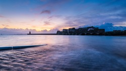 A breathtaking sunset over the historic Castle Cornet at the seashore in Guernsey