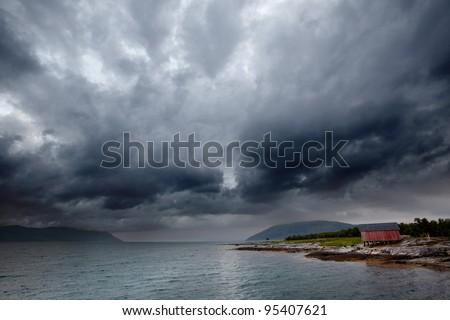 A brewing storm on an ocean sunset - stock photo