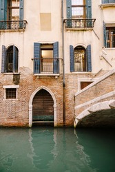 A brick building in the water in Italy, Venice. A brick bridge over a small narrow canal, classic Venetian windows in the facade of the building with wooden shutters and forged bars.