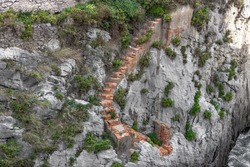 A brick staircase among the stones. Ruined steps of the castle along the cliff. Descent to the sea. Fragments of a medieval building. Difficult climb. Path in the mountain. The road to nowhere.