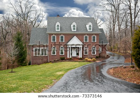 A brick two-story house in a secluded wooded setting with an asphalt driveway on a wet, rainy winter day.