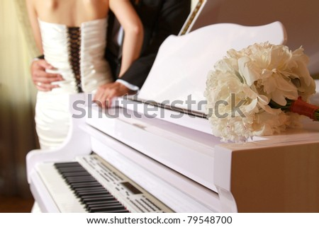 A bride and a groom near a white piano, focus on the flower bunch