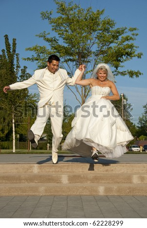 A bride and groom celebrate their wedding in a park
