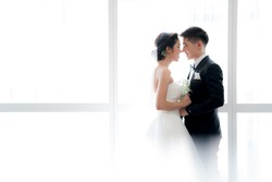 A bride and groom kissing over large bright window.