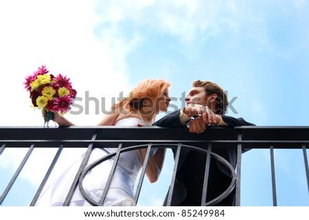 A bride and groom on a balcony